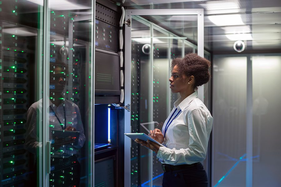 Cyber Security Contractor Insurance - Technician Working on a Tablet in a Data Center Full of Servers Running Diagnostics and Maintenance