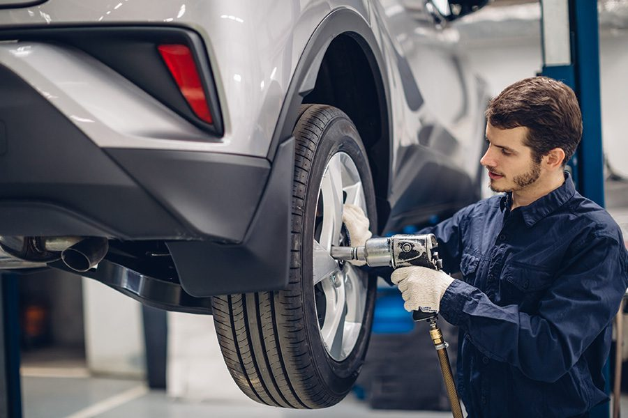 Blog - Mechanic Changing a Tire on a Silver Car at an Auto Car Repair Service Center
