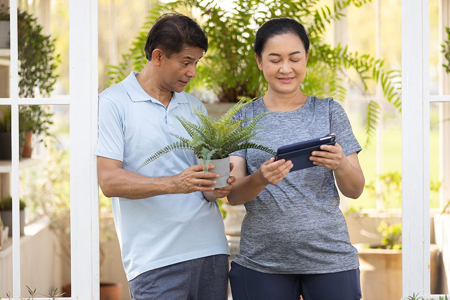 Client Center - Senior Couple Smiling While Holding Plant Pots and Using a Tablet in Their Garden