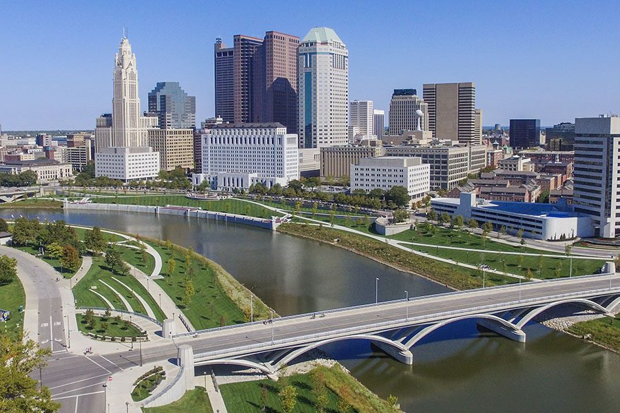 Contact - Aerial View of Columbus Ohio Skyline Displaying Many Tall Buildings, a Bridge That Crosses Over a Large River on a Bright Clear Day