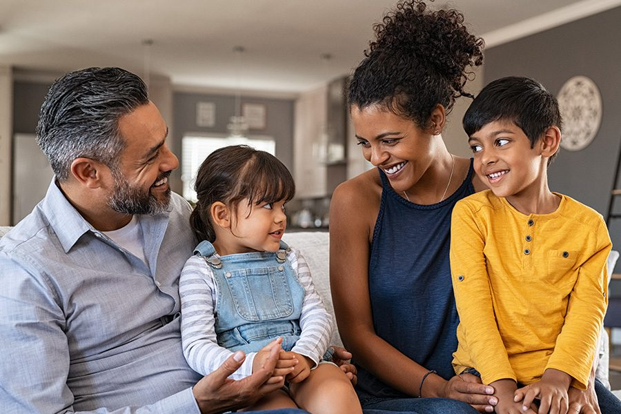Personal Insurance - Happy Family With Kids Sitting Down on Sofa Smiling and Laughing