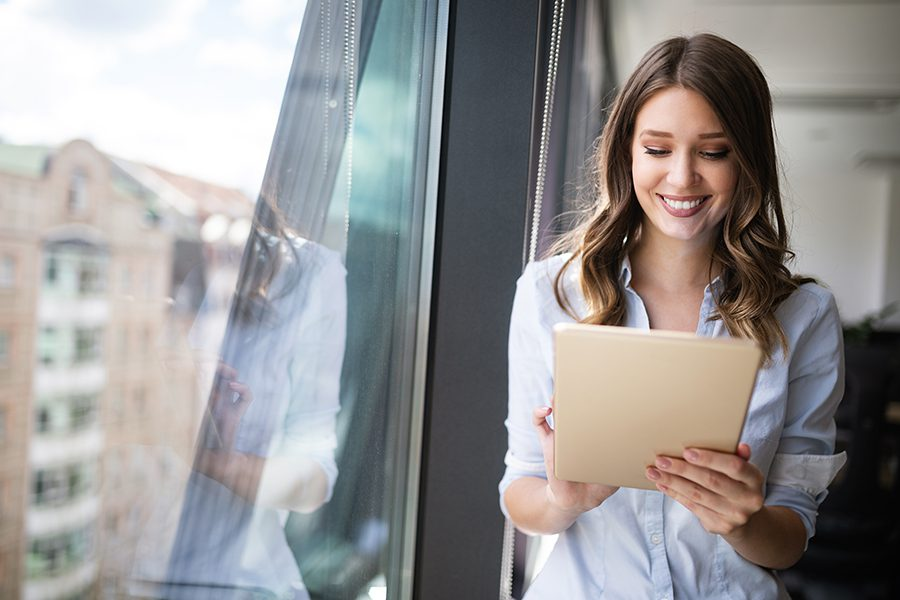Client Center - Happy Woman Holding Tablet and Standing in Her Modern Office