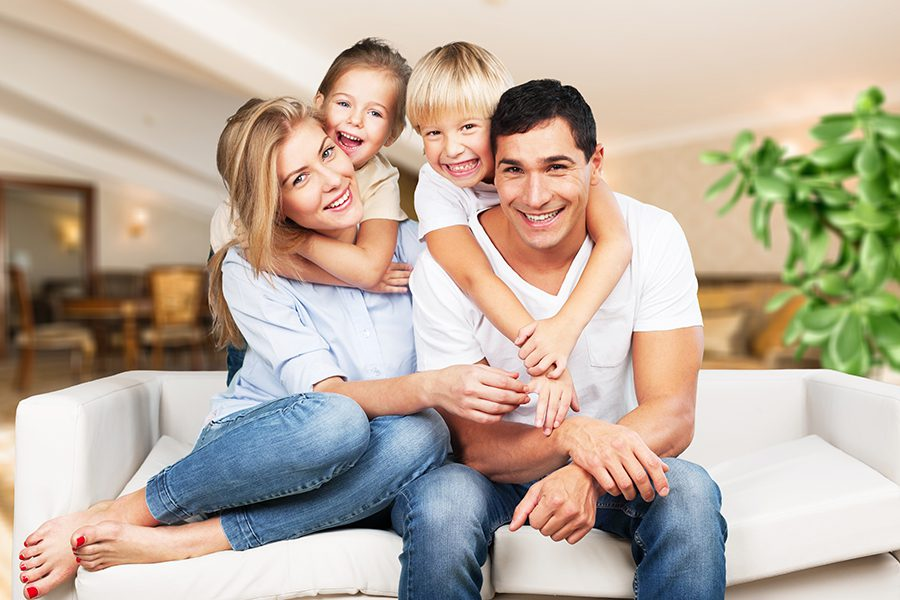Personal Insurance - Portrait of a Young Family at Home Smiling and Sitting on the Sofa in Their Living Room