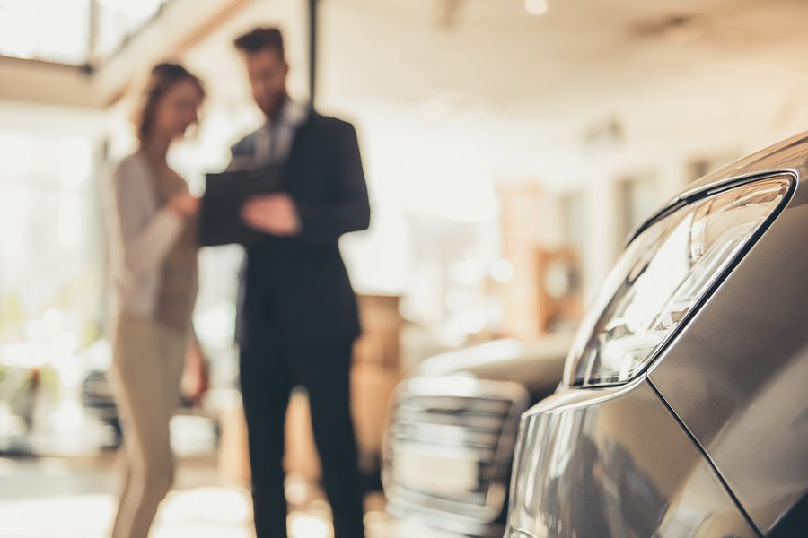 Specialized Business Insurance - Woman Going Over Insurance Details In Car Showroom After Purchasing a New Car