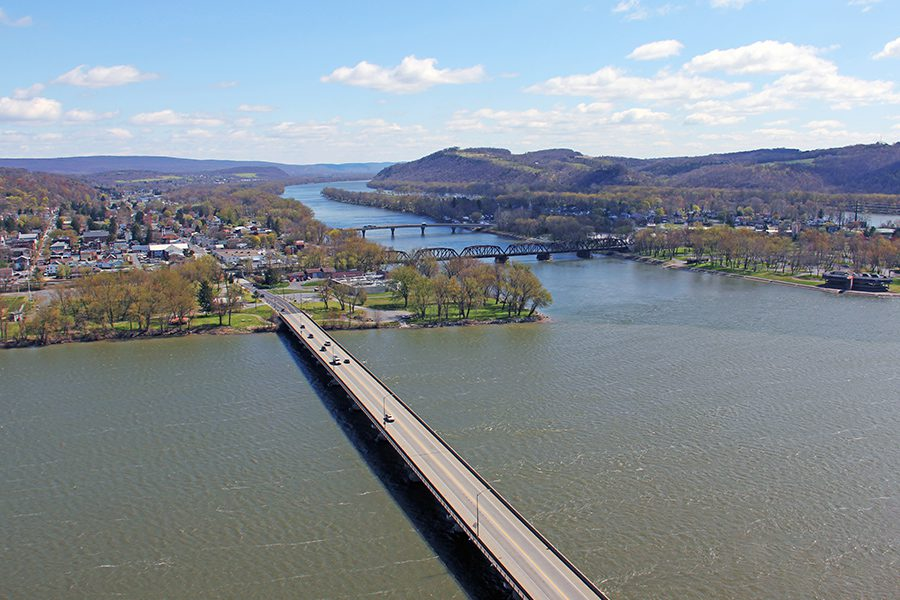 Contact - Aerial View of Rural Town with Trees and Susquehanna River in the Background