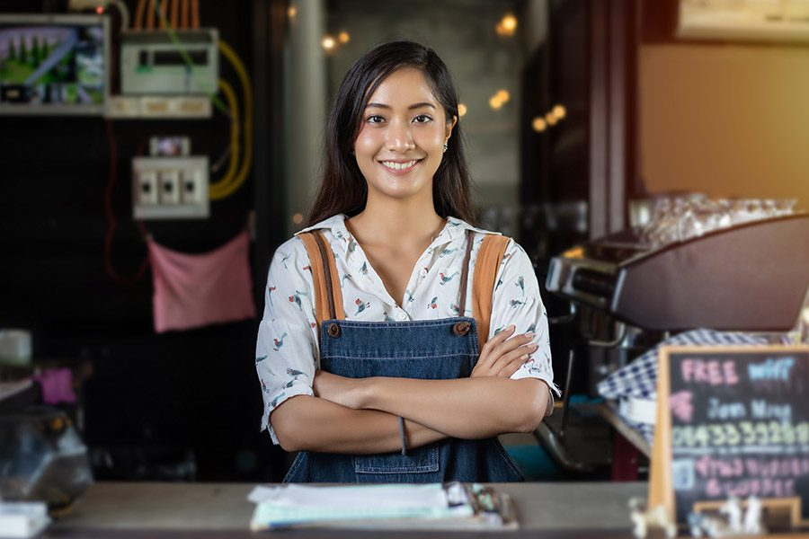 Business Insurance - Women Barista Smiling and Using Coffee Machine in a Coffee Shop from behind the Counter