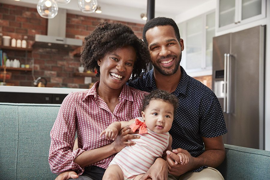 Personal Insurance - Portrait of Family with Baby Daughter Relaxing On Sofa at Home Together