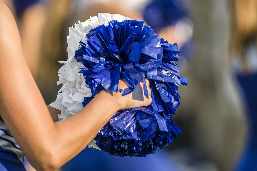 Cheer Gym Insurance - Woman Holding Blue and White Pom Poms at the Cheer Gym