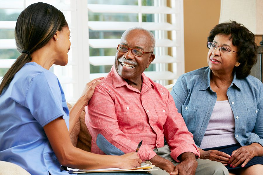 Senior Care Facility Insurance - Home Nurse Meeting with Older Couple in the Living Room