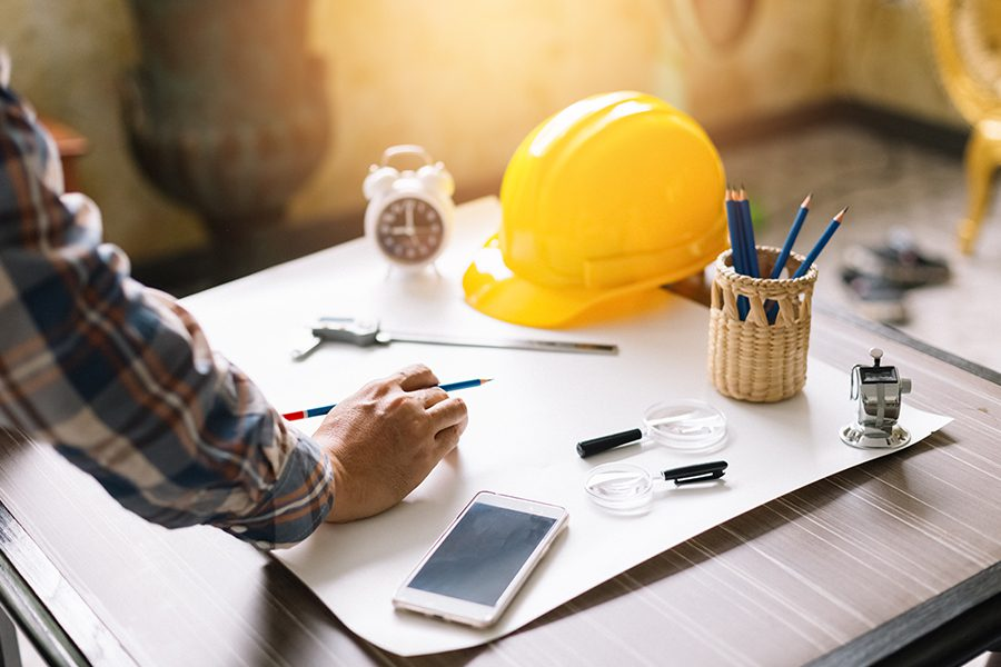 Specialized Business Insurance - Construction Engineer Sketching a Construction Project on a Drawing Table with Engineering Tool in the Office