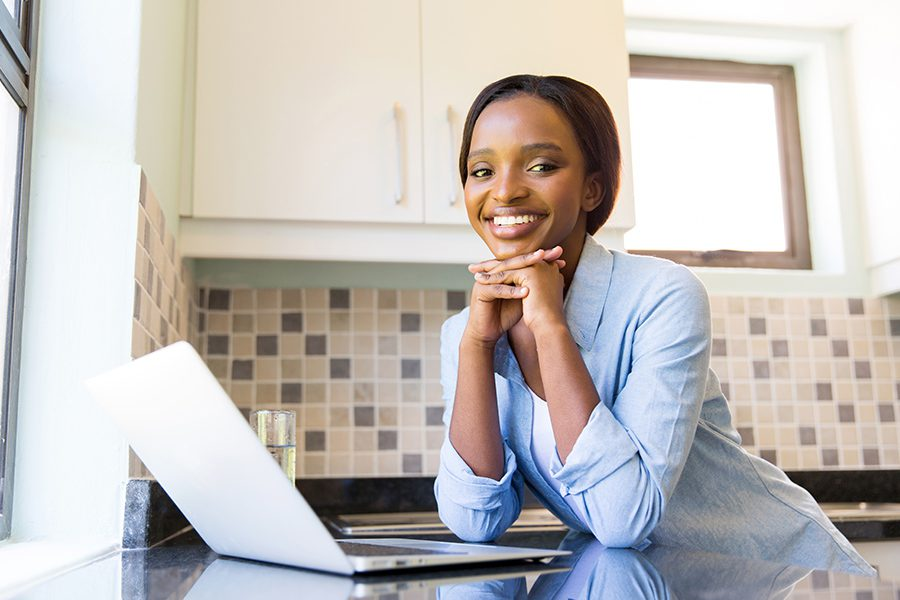 Client Center - Young Woman Using Her Laptop in Her Modern Kitchen
