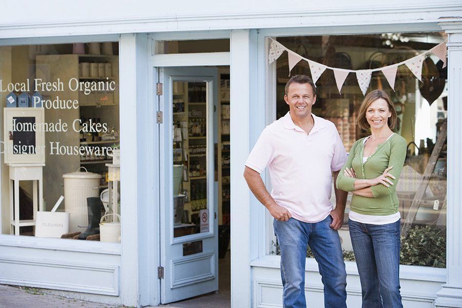 Business Owners Insurance - Smiling Couple Standing in Front of Organic Food Store