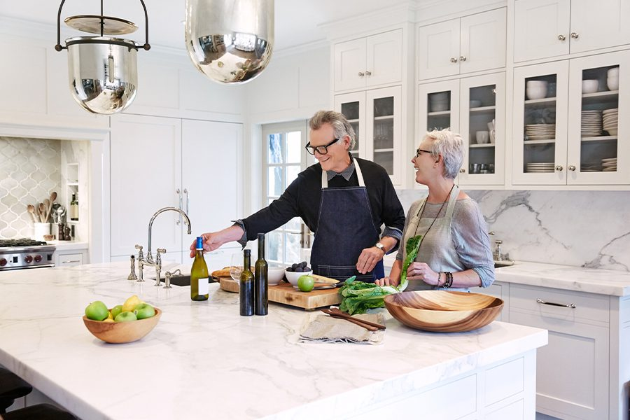 High Net Worth Insurance - Mature Couple Cooking in Modern Kitchen of Their Luxury Home