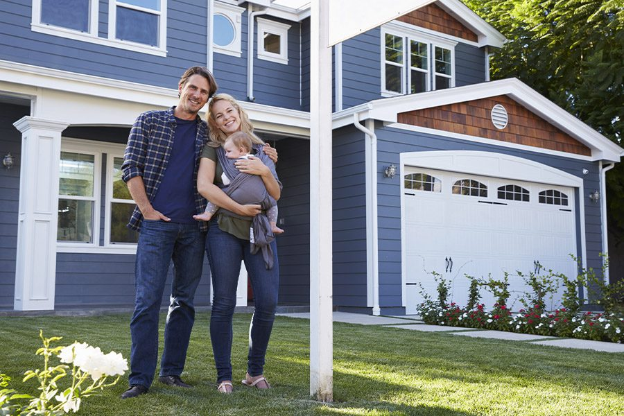 Home Insurance - Portrait of Family Standing Outside House