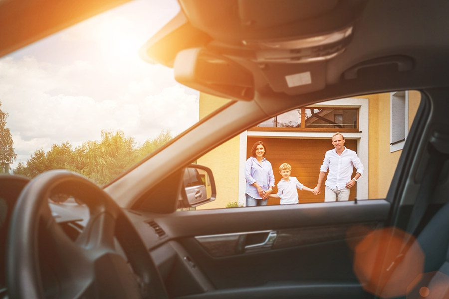 Home and Auto Insurance (Bundled) - From Inside the Car View of a Young Family Going to Their Car Standing in the Yard