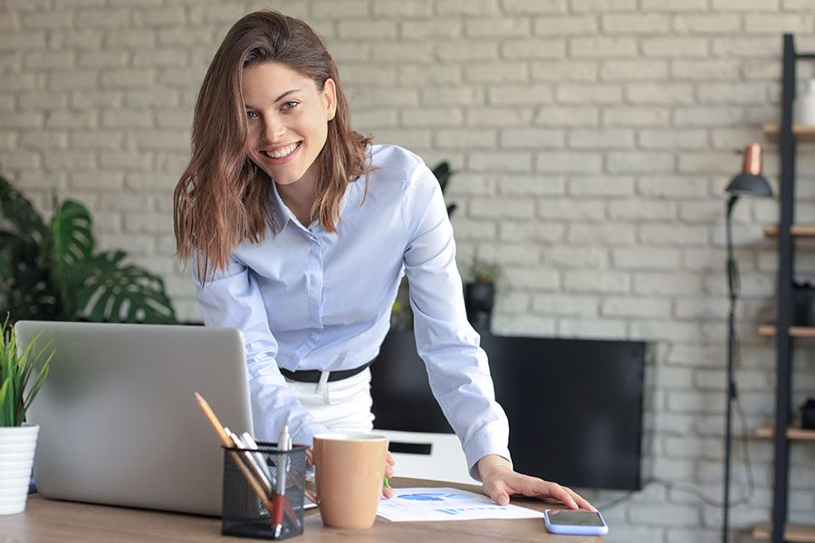 Business Insurance in Hanover, NH - Young Business Woman Standing in Her Home Office Writing Notes