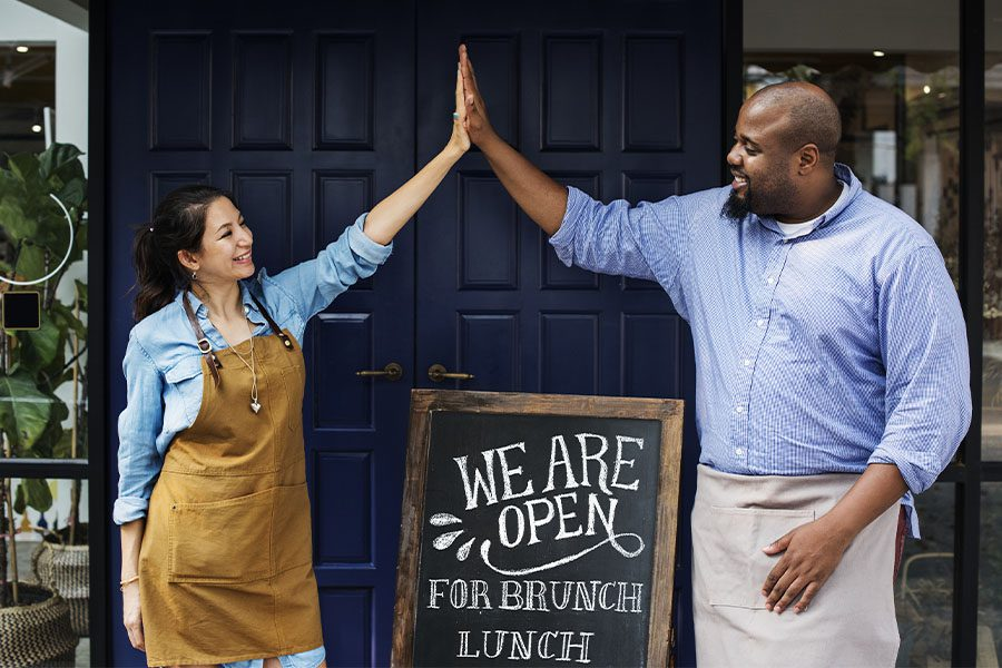 Business Insurance in New Hampshire - Cheerful Business Owners Standing with Open Sign Blackboard