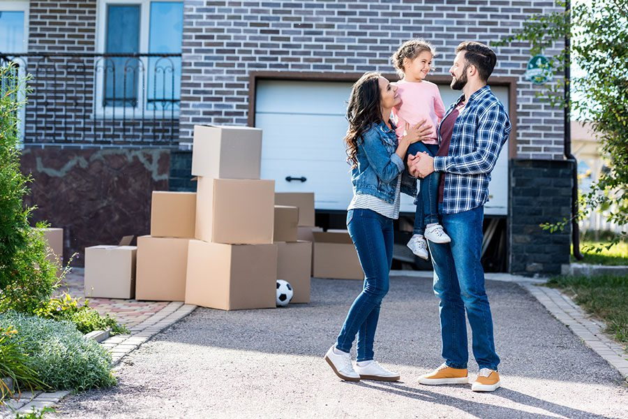 Peninsula Insurance Group - Young Family Standing with Boxes Outside of their New Home