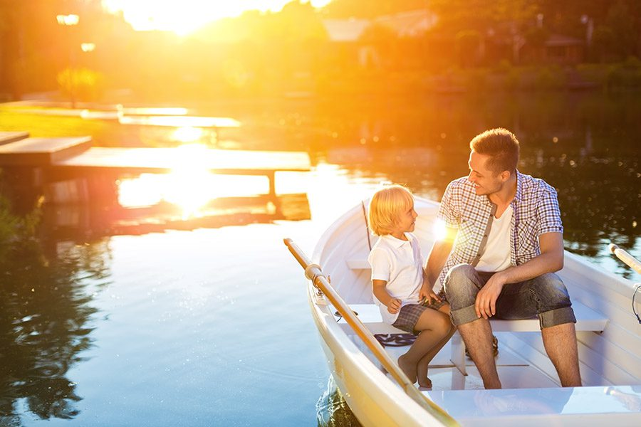 Life-Insurance-Agency-New Hampshire-Father-and-Sun-Riding-in-a-Boat-on-a-Lake-at-Sunset