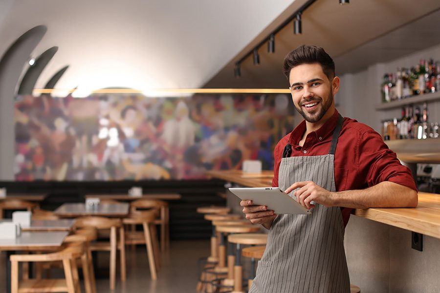 General Liability Insurance in New Hampshire - Business Owner in Restaurant Working on IPad