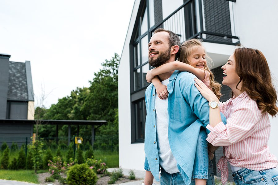 Homeowner's Insurance in New Hampshire - Happy Family Together Outside Their New Modern Home