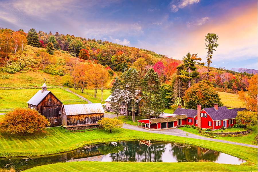 Insuring Vermont - Beautiful Vermont Farm House with Brown Barn Infront of a Lake in the Fall with a Rainbow in the Sky