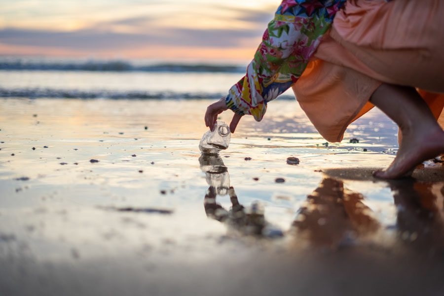Environmental Insurance - Woman Picking Up Bottle at the Beach