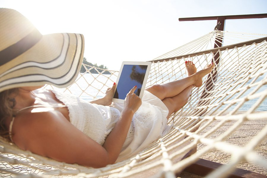 Client Center - Woman Using Tablet in a Hammock on the Beach