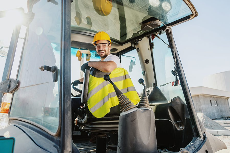 Specialized Business Insurance - Smiling Worker in Overalls with Helmet Driving an Excavator on Construction Site on a Bright Sunny Day