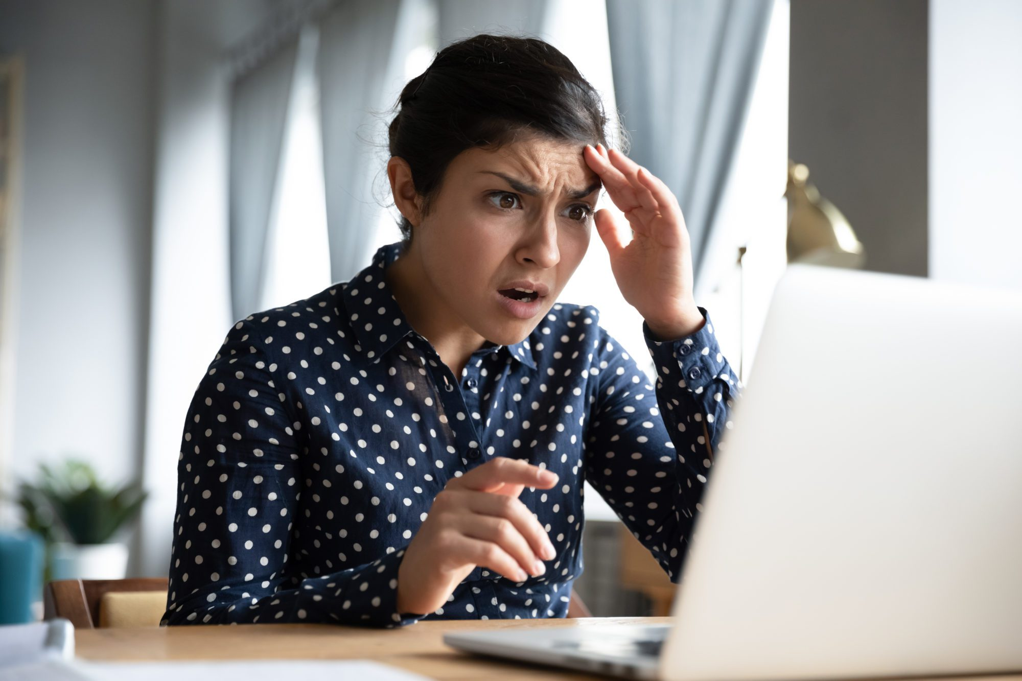 Shocked girl look at laptop computer screen at home office
