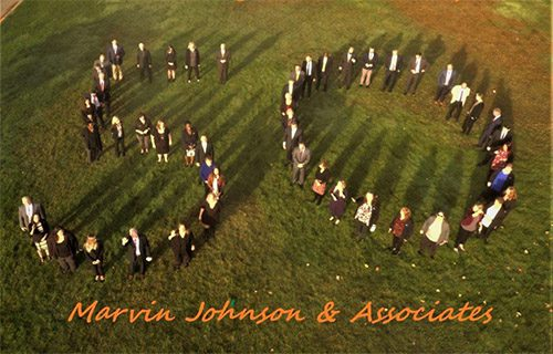 About Our Agency - Team Members of Marvin Johnson & Associates Celebrating Their 50th Anniversary by Standing in the Shape of the Number 50 in a Field on a Beautiful Day