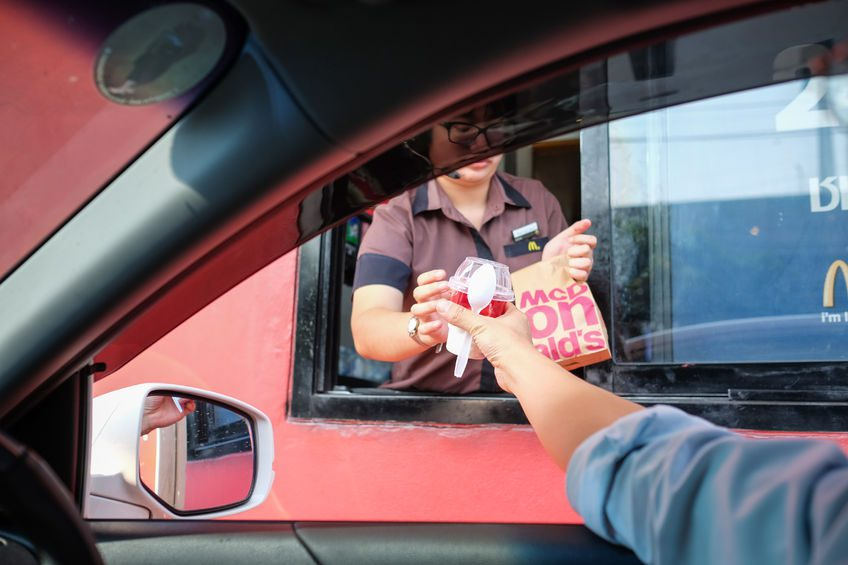 nidentified customer receiving hamburger and ice cream after order and buy it from mcdonald's drive thru service, mcdonald's is an american fast food restaurant chain