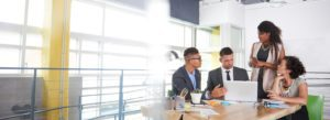 Header - Business Insurance Employees Sitting at a Table Working