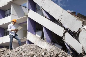 Natural-Disaster-Insurance-Engineer-Looking-Over-the-Rubble-with-an-iPad-in-Hand