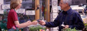 Header - People Exchanging Money in a Flower Shop