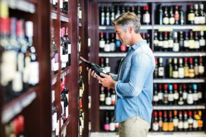 Liquor Store Insurance - Middle Aged Handsome Man Picking Out Wine In A Liqu0r Store
