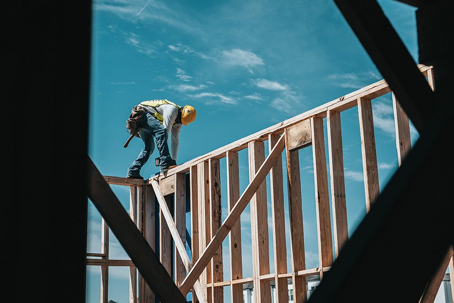 Blog - 6 Weather Resistant Building Materials to Protect Your Home - Worker Building a House Frame