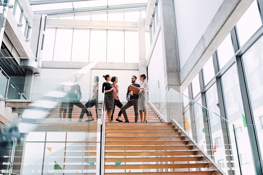 Business Insurance - View of Group of Coworkers Standing on the Stairs Talking in a Modern Office