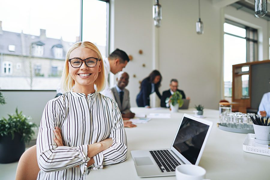 Contact - View of Cheerful Business Woman Next to Her Laptop Sitting in a Modern Office With Views of Her Business Colleagues in the Background