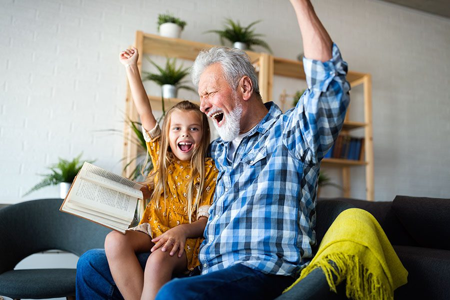 Employee Benefits - Grandfather and Granddaughter Sitting on the Sofa Having Fun Reading a Book Together