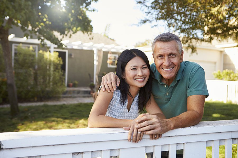 Homeowners Review Questionnaire - Portrait of Cheerful Couple Standing Next to a White Picket Fence in Their Backyard