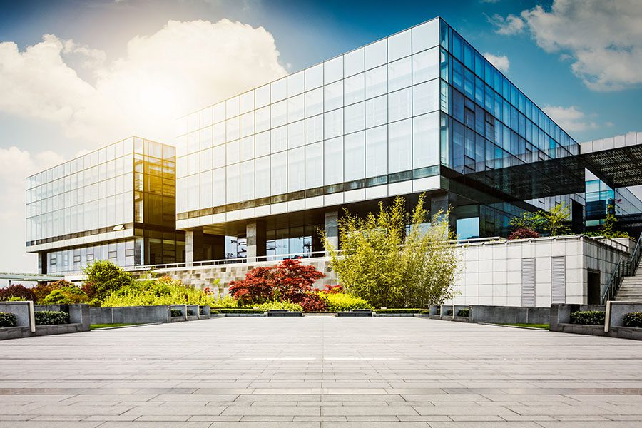 Specialized Business Insurance - View of a Modern Glass Office Building Against Blue Sky with Green Landscaping in the Front