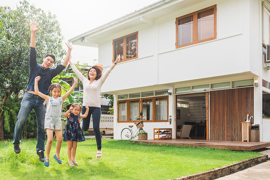 Home Insurance - Family Jumping for Joy in Front of Their House on a Sunny Day