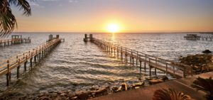 Header - Long Wooden Docks Stretching Out into Galveston Bay at Sunset
