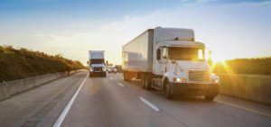 Trucking-Insurance-Banner-Two-Trucks-Rolling-Down-the-Highway
