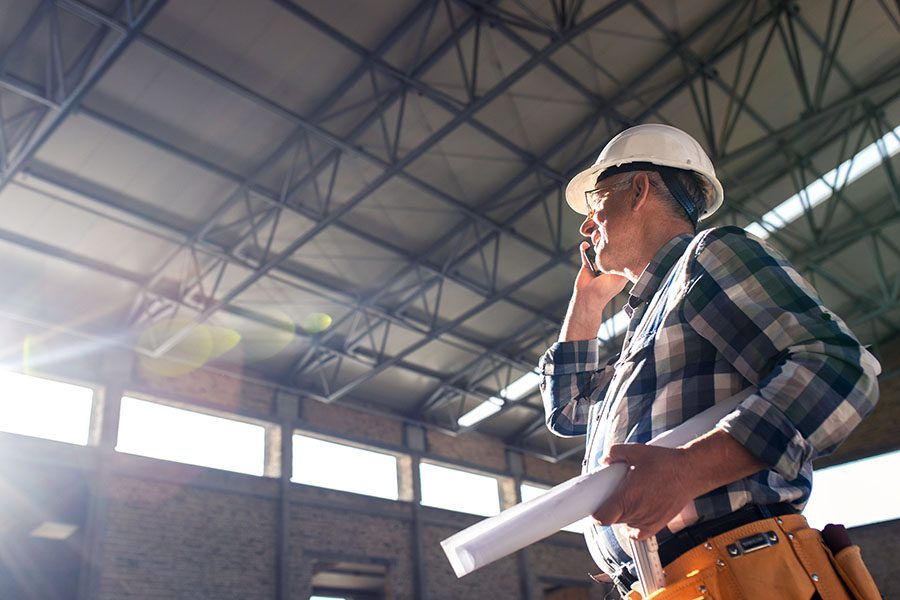 Specialized Business Insurance - View of Contractor Talking on the Phone Holding Construction Plans at a Building Jobsite
