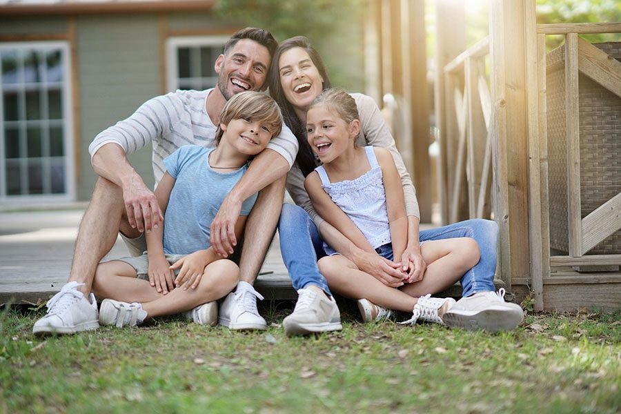 Personal Insurance - Happy Family Sitting In Backyard