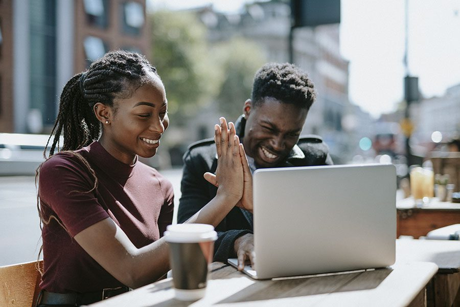 Client Center - Two Friends Sitting at a Cafe with a Laptop Giving Each Other High Five While Celebrating Success