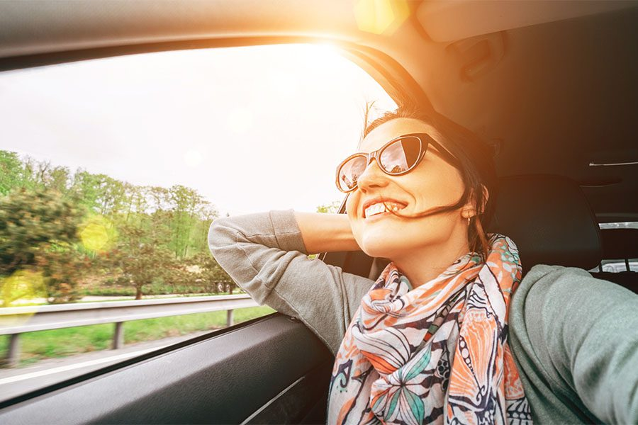 Insurance Quote - View of Joyful Woman Looking Out the Window During a Road Trip on a Sunny Day