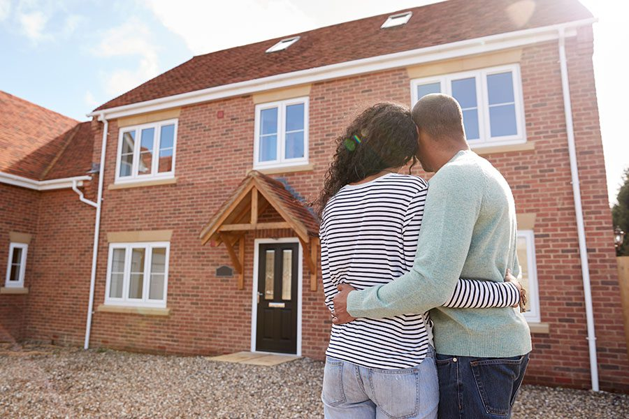 Personal Insurance - Young Couple Standing Outside Looking at Their New Two Story Home
